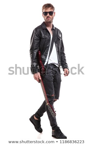 handsome fashion man stepping to side while holding guitar stock photo © feedough