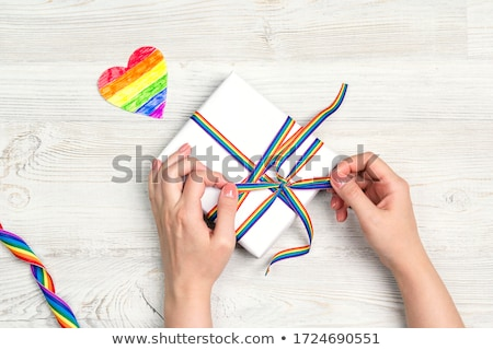 female hands and present with gay awareness ribbon Stock photo © dolgachov