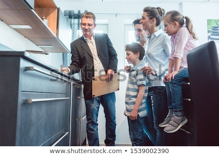 Salesman showing family the features of a new kitchen  Stock photo © Kzenon