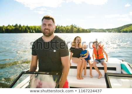 Stock photo: Man driving boat on holiday with his son kids and his wife