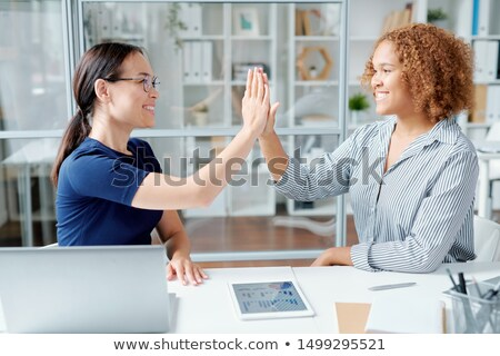 Two young multicultural bankers giving high five to each other after work Stock photo © pressmaster