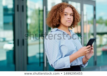Young serious intercultural businesswoman with smartphone messaging outdoors Stock photo © pressmaster