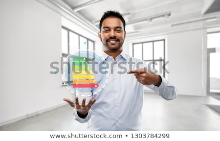 realtor with energy levels over empty office room Stock photo © dolgachov