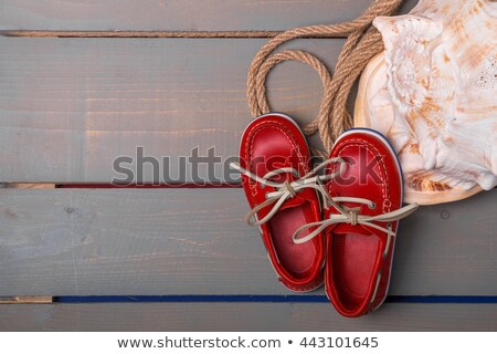 Red boat shoes near big shell and rope on wooden background. Top view/. Copy space. Frame. Stock photo © Illia