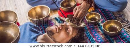 BANNER, LONG FORMAT Nepal Buddha copper singing bowl at spa salon. Young beautiful man doing massage Stock photo © galitskaya