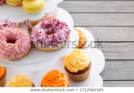 close up of glazed donuts and cupcakes on stand Stock photo © dolgachov