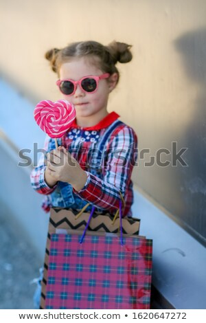 Child with Lollipop on a stick in his hands on the background of the wall Stock photo © ElenaBatkova