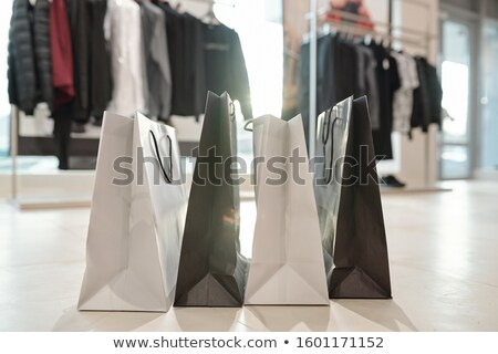 Row of black and white paperbags standing on the floor of boutique Stock photo © pressmaster