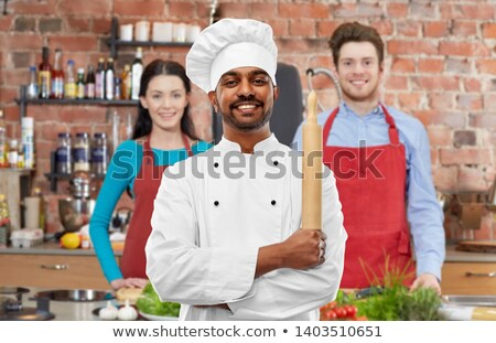 male indian chef with rolling-pin at cooking class Stock photo © dolgachov