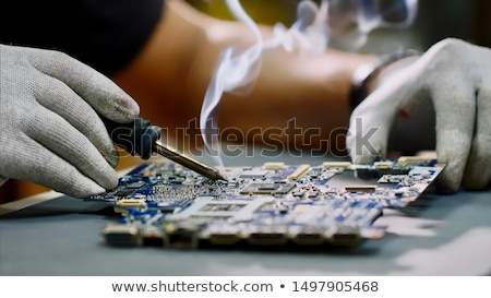 Engineer or technician repair electronic circuit board with soldering iron. Stock photo © Illia