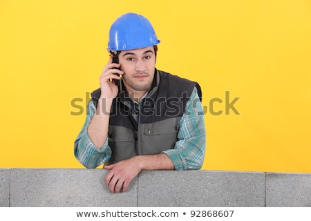 Builder stood by unfinished wall making telephone call Stock photo © photography33