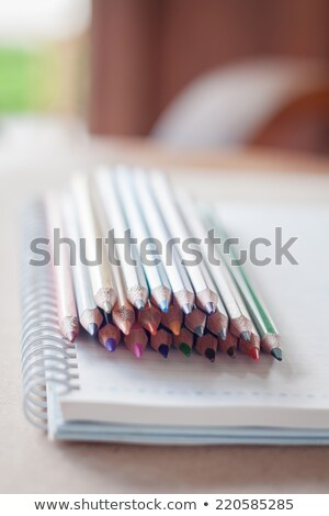 cluster of colorful pencil crayons on spiral notebook stock photo © punsayaporn
