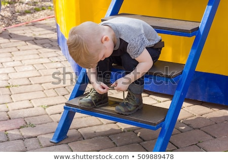 Boy Sitting On Stairs Tying Shoelaces Stock photo © HighwayStarz