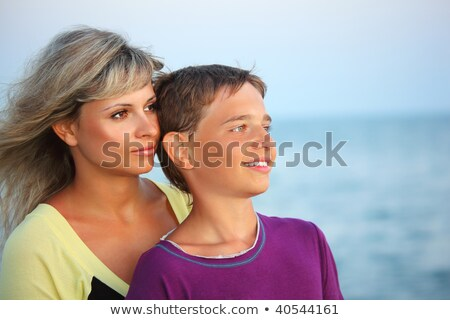 smiling boy and young woman on beach in evening looking afar stock photo © paha_l
