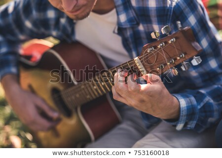 Stock photo: Male hands playing on guitar outdoors