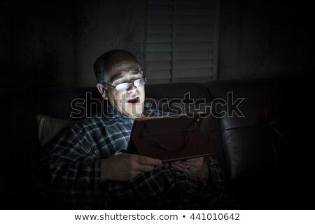 Yawning man reading tablet at night Stock photo © elenaphoto