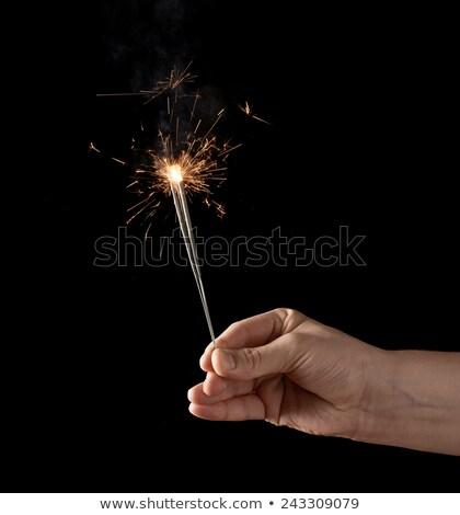 hand holding sparkler over black background Stock photo © dolgachov