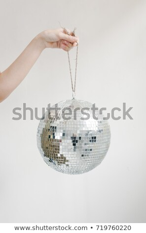 Hand holding disco ball on string isolated on white background stock photo © Sibstock