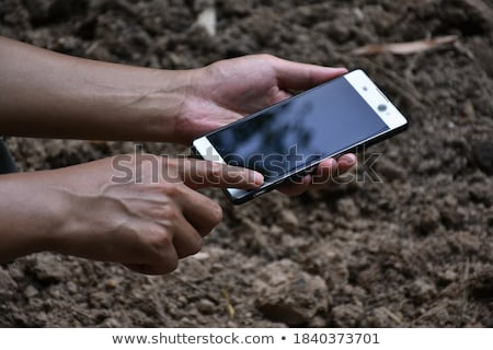 Farmer holding blank screen mobile phone over soil ground Stock photo © stevanovicigor
