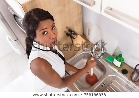 unhappy woman using plunger in clogged sink stock photo © andreypopov