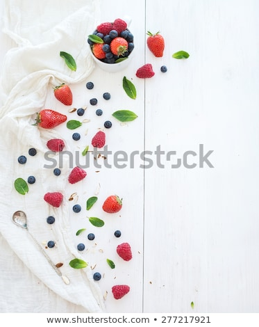 raspberries on spoon with mint leaves on blue background stock photo © denismart