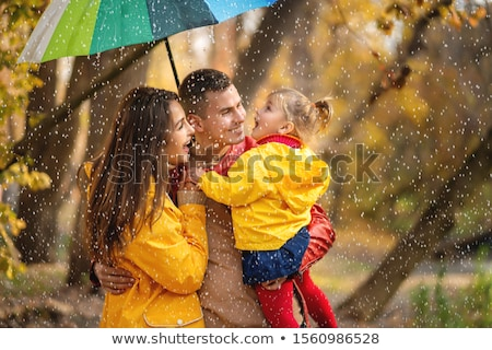 A family under an umbrella in the rain Stock photo © IS2