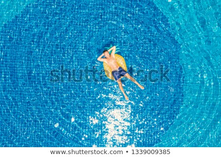 Happy young man floating on blue water Stock photo © Sonya_illustrations