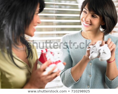 Two mothers comparing baby shoes Stock photo © IS2