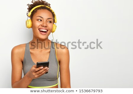 Happy curly brunette fitness woman listening music and looking away Stock photo © deandrobot