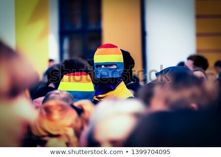 man in a car waving a rainbow flag