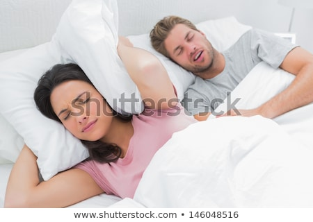Woman Covering Her Ears While Man Snoring On Bed Stock photo © AndreyPopov
