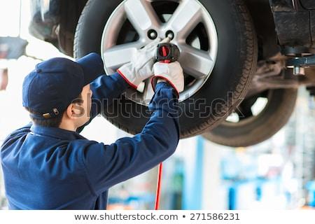 Mechanician changing car wheel in auto repair shop Stock photo © Minervastock