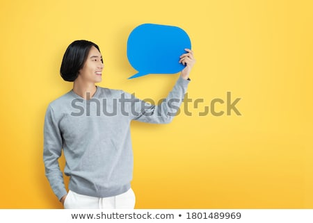 happy young asian man standing isolated over yellow background holding speech bubble stock photo © deandrobot
