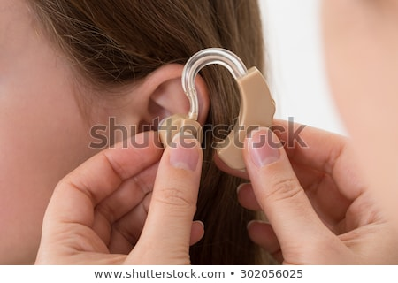Close-up Of A Girl Holding Hearing Aid Stock photo © AndreyPopov