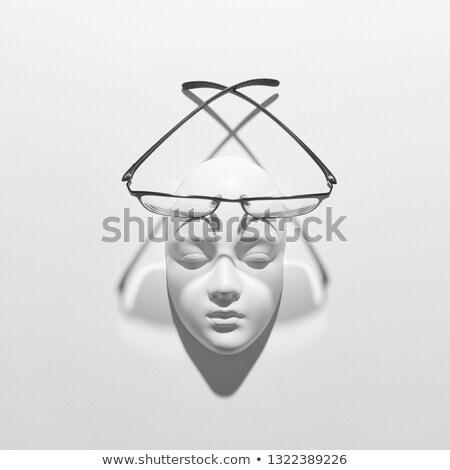 Elegant glasses on a gypsum face sculpture with long shadows on a white background, copy space. Top  Stock photo © artjazz