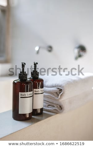 Close up view on the bottles with shampoo, shower gel and towels in the hotel bathroom Stock photo © galitskaya