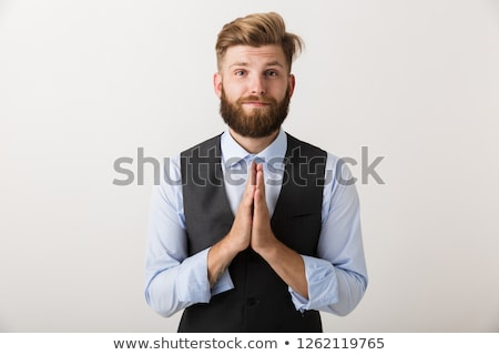 Young bearded man standing isolated over white wall background make hopeful please gesture. Stock photo © deandrobot