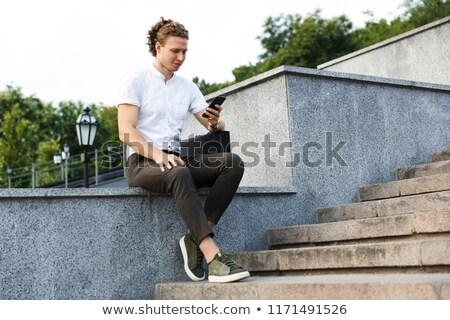 Komoly fürtös üzletember aktatáska okostelefon ül Stock fotó © deandrobot