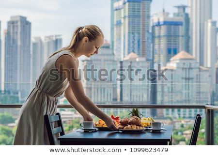 Stockfoto: Young woman is laying on a table. Breakfast table with coffee fruit and bread croisant on a balcony