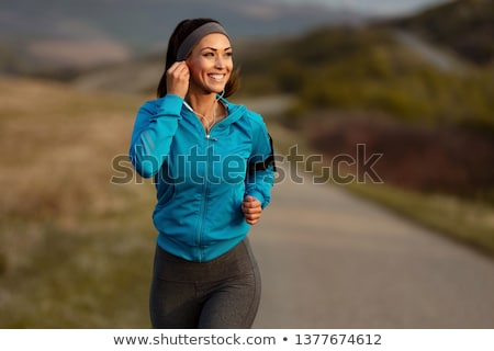 Happy young sports woman listening music with earphones. Stock photo © deandrobot