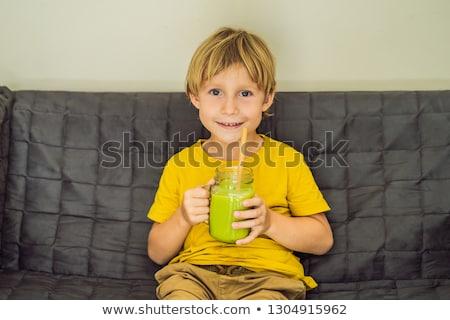 The boy is drinking Green tea latte with ice in mason jar. Homemade Iced Matcha Latte Tea with Milk  Stock photo © galitskaya