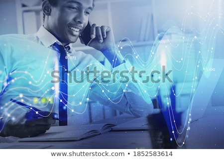 Young banker or financier with papers studying financial charts and graphs Stock photo © pressmaster