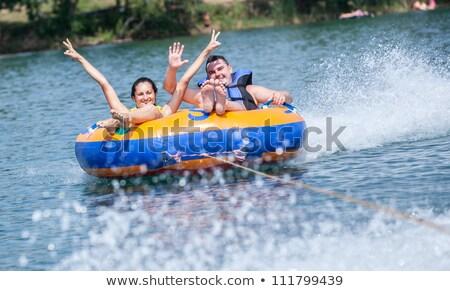 Man and Woman Riding on Inflatable Banana on Sea Stock photo © robuart