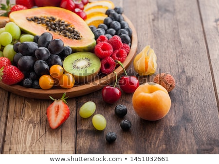 Fresh raw organic summer berries and exotic fruits in round wooden plate on wooden kitchen backgroun Stock photo © DenisMArt