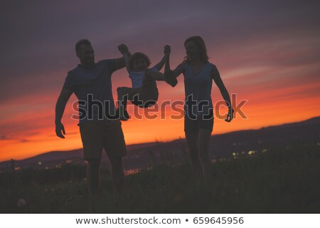 Mother and Father swinging son up in the air at sunset stock photo © Lopolo