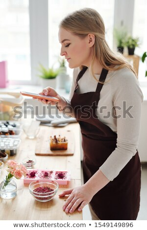 Pretty creative woman with smartphone taking photo of handmade soap on table Stock photo © pressmaster