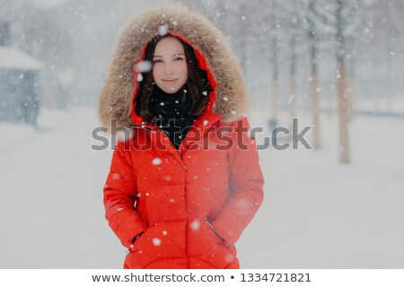 Waist up shot of attractive smiling woman with healthy skin, dark hair, wears red jacket, keeps hand Stock photo © vkstudio