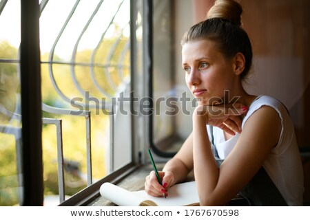closeup portrait of a young woman sitting at her workplace near stock photo © hasloo