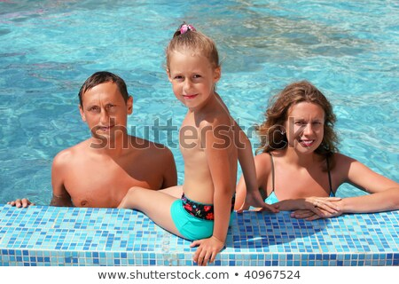 Happy family with little girl bathe in pool, daughter sits near  Stock photo © Paha_L