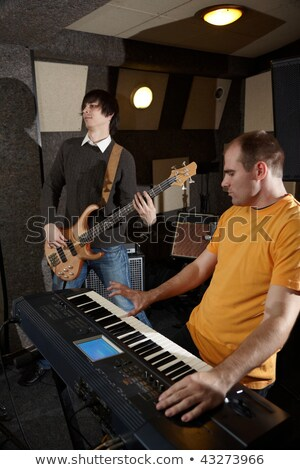 Guitar player and keyboard player is working in studio. focus on distant part of synthesizer Stock photo © Paha_L